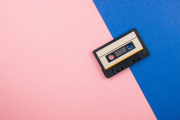 Retro audio cassette flat lay on colorful blue pink pastel background. top view with copy space. creative fashion design in minimal 80-s style with duotones.