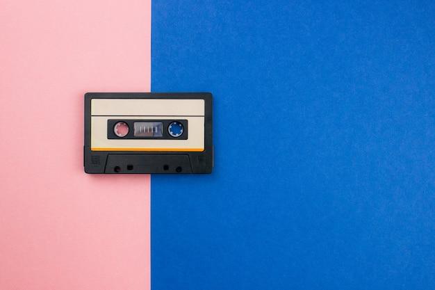 レトロなオーディオカセットフラットは、カラフルなブルーピンクのパステルカラーの背景に横たわっていた。コピースペースのある上面図。ダブルトーンを使用した最小限の80年代スタイルのクリエイティブなファッションデザイン。