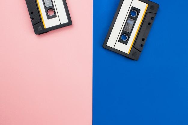 Ретро аудиокассета плоская лежала на красочном голубом розовом пастельном фоне. вид сверху с копией пространства. креативный модный дизайн в минималистичном стиле 80-х с дуотонами.
