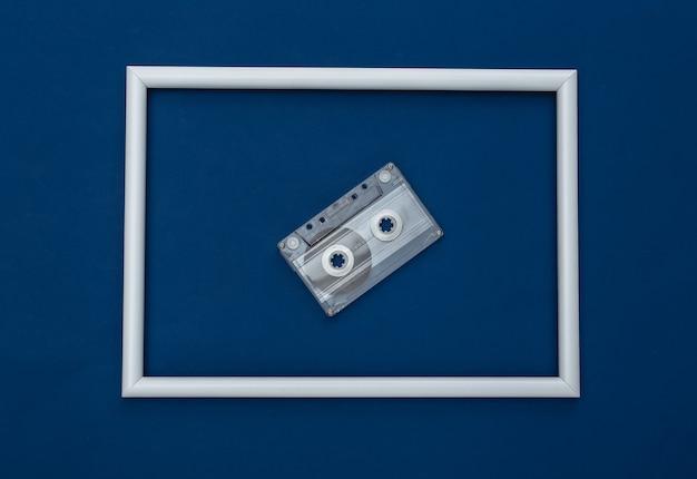 흰색 프레임이 있는 고전적인 파란색 배경의 복고풍 오디오 카세트. 컬러 2020. 탑 뷰