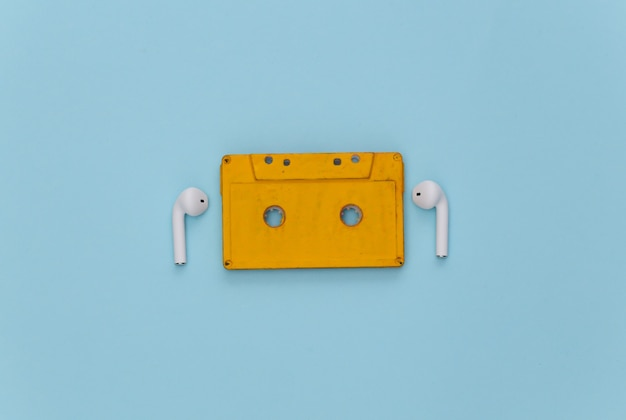 Retro audio cassette and wireless earphones on blue background.