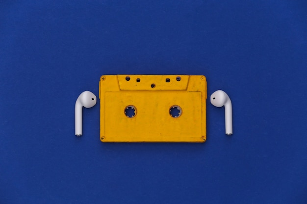 Retro audio cassette and wireless earphones on classic blue background.