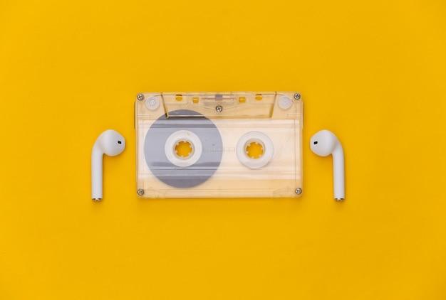 Retro audio cassette and wireless earphones on yellow background.