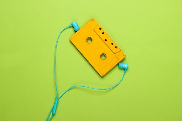 Retro audio cassette with earphones on green pastel