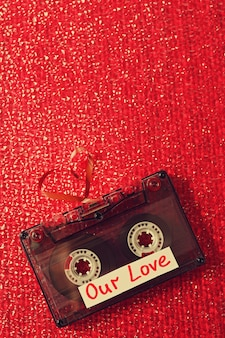 Retro audio cassette with tape in shape of heart on red textured surface