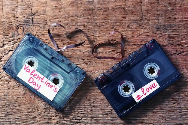 木製の背景にハートの形のテープとレトロなオーディオカセット