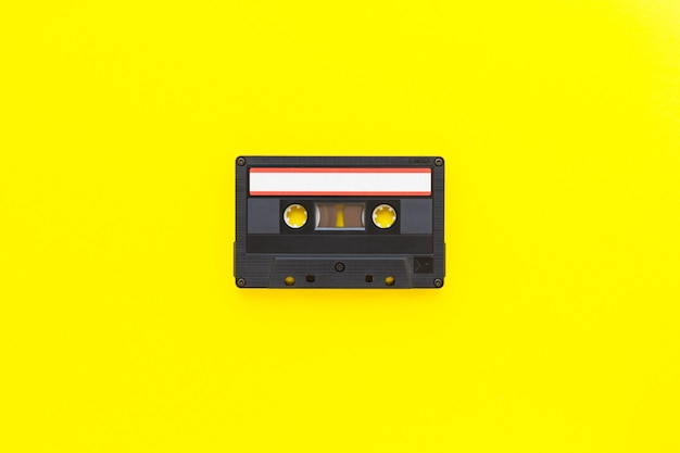 Retro audio tape cassette from 80s and 90s isolated on yellow background. old technology concept. flat lay, top view with copy space.