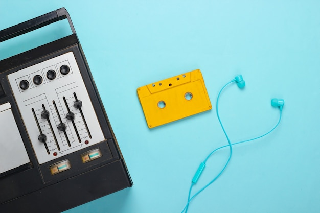 Retro audio tape recorder, earphones and audio cassette. retro media on blue