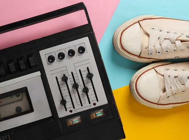 Retro audio tape recorder and old sneakers. retro media on colored