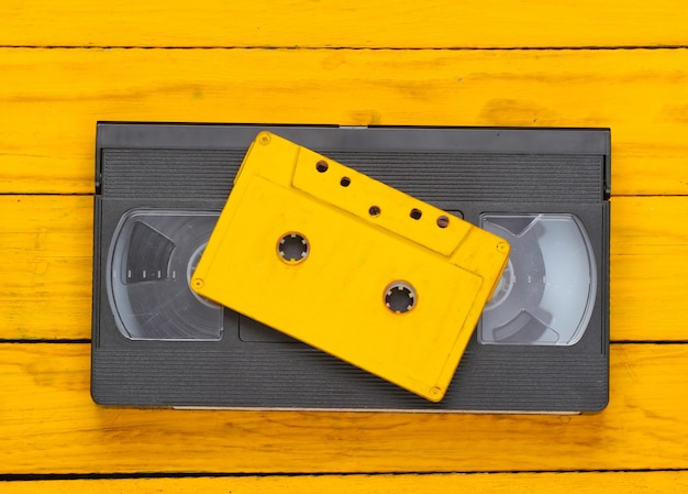 Retro audio and video cassette on a yellow wooden