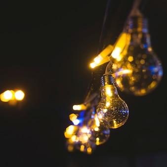 Ретро красивая лампа огни на гирлянду на черном фоне.