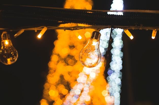 Ретро красивая лампа загорается на фоне ярких огней городской елки.