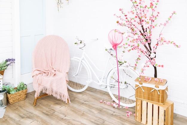 꽃 담요 아래 복고풍 자전거와 고리 버들 세공 안락의 자