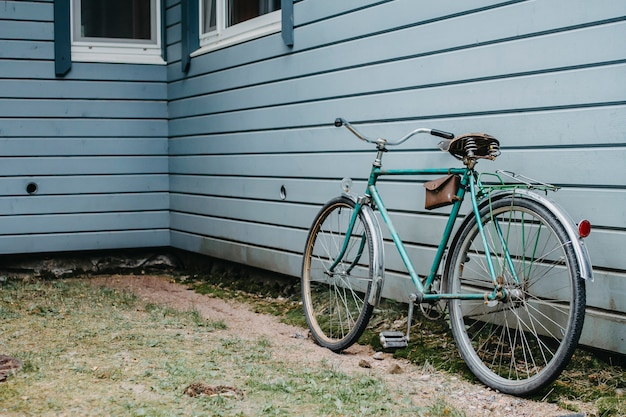 Retro bicycle stands against a blue wall