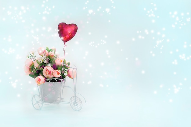 Retro bicycle with basket of flowers and heart-shaped balloon on light magic background.