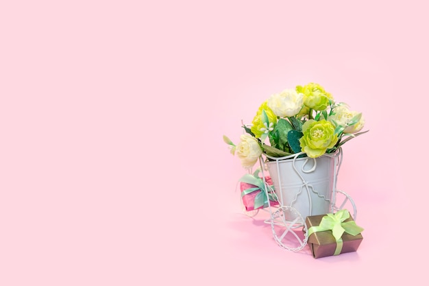 Retro bicycle with pot of bouquet flowers and gift boxes on pink background