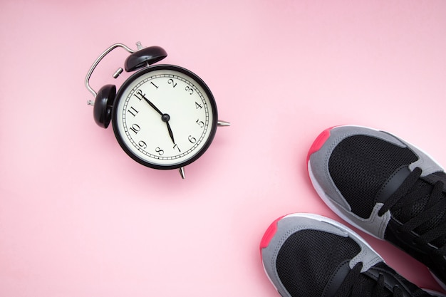 Retro black alarm clock and black with raspberry sneakers on a pink background.