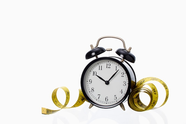 白い背景の上の黄色の測定テープとレトロな黒の目覚まし時計成功の概念