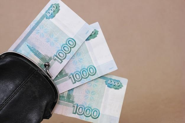 レトロな黒い財布と額面1000ルーブルの3枚の紙幣が突き出ています。ビジネスと金融、富の概念。