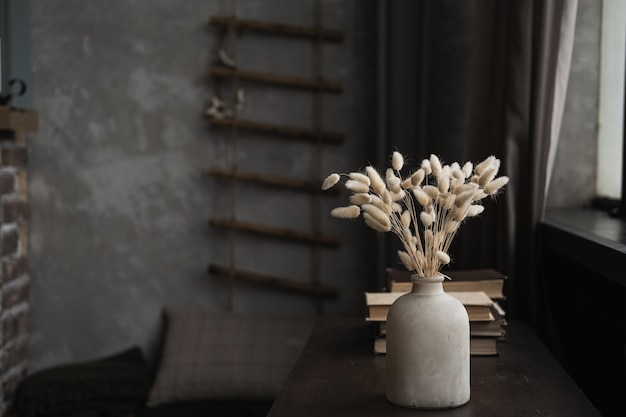Retro bottle with rabbit tail grass bouquet, books on dark brown table.