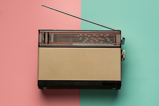 Retro broadcast radio receiver on pink and light blue background