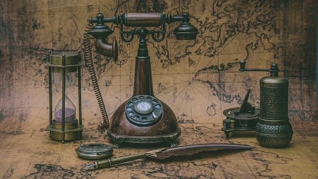 Retro bronze telephone and old collection on old world map