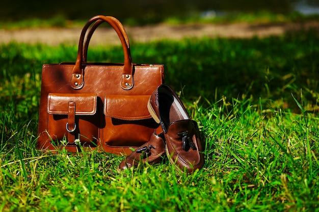 レトロな茶色の靴と公園の明るいカラフルな夏の草の男革バッグ