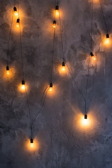 Retro bulbs in the form of a garland on a gray concrete.