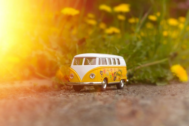 Retro bus toy on blooming dandelions in the sunlight