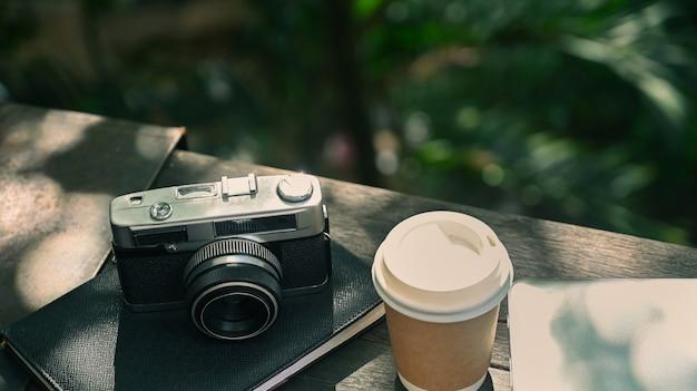 자연 야외 공원의 나무 테이블에 있는 복고풍 카메라와 커피 한 잔.