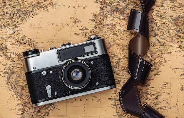 古い地図上のレトロなカメラとフィルムテープ。旅行のコンセプト
