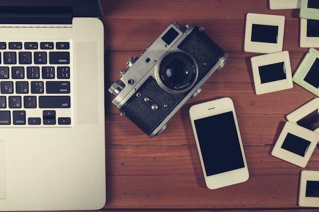 レトロなカメラと木製のテーブルにいくつかの古い写真