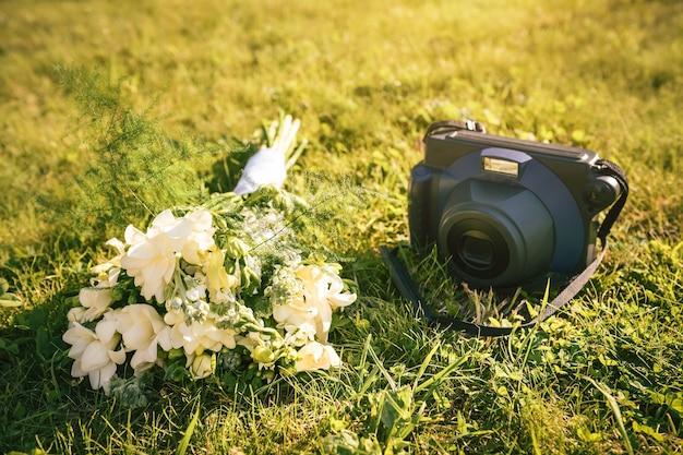 緑の草の上のレトロなカメラとウェディングブーケ