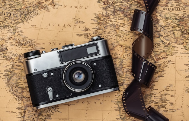 Retro camera and film tape on old map. travel concept
