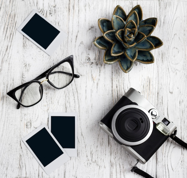Retro camera, glasses and empty old instant paper photo