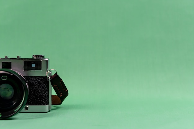 Retro camera on green background