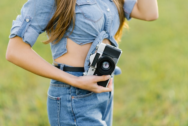 Retro camera in the hands of a girl in denim clothes. the traveler or travel blogger with a camera