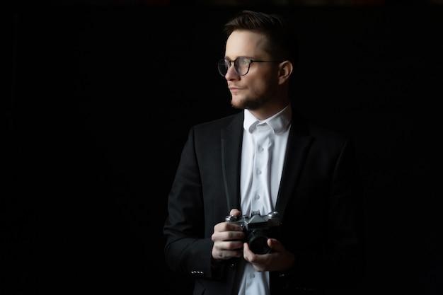 Retro camera in hands of handsome bearded elegant man in suit