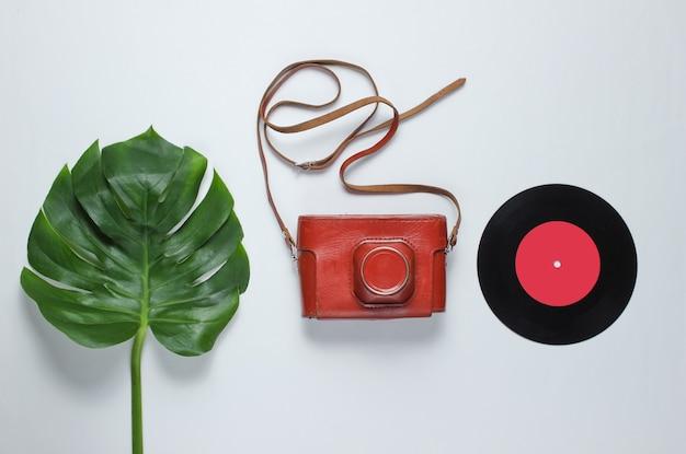 Ретро фотоаппарат в кожаном футляре с ремешком, виниловая пластинка и зеленый лист монстера на белом фоне. винтажный стиль плоской планировки. вид сверху