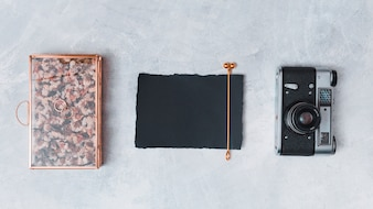 Retro camera near dark paper and creative box