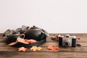 Retro camera near leaves and tea set