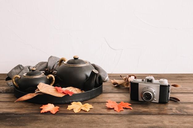 Retro camera near leaves and tea set