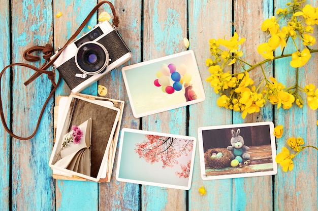 Retro camera and paper photo album on wood table with flowers