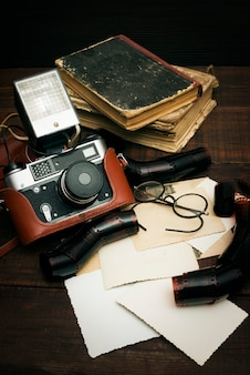Retro camera and some old photos on wooden table surface