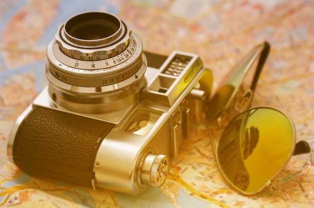 Retro camera and sunglasses on a map