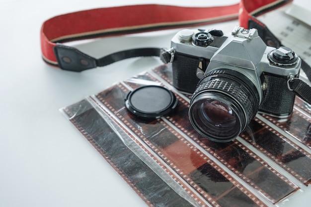 フィルムネガロールに赤いストラップが付いたレトロなカメラ。コピースペース