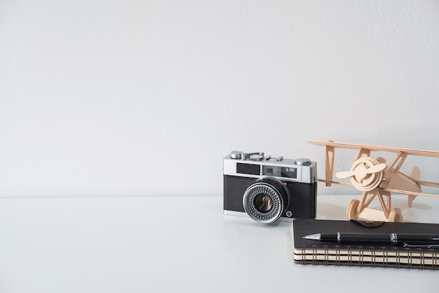 Retro camera with toy plane and notebook with copy space, travel concept