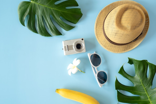 Retro camera with toy plane on pastel blue background with copy space summer vacation concept