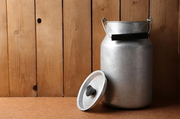 木製のテーブルの上のミルクのためのレトロな缶