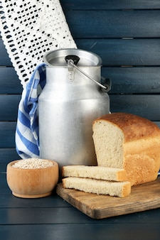 Retro can for milk with fresh bread on wooden table. bio products concept